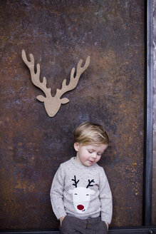Portrait of young boy, cardboard reindeer cut out on wall behind him - CUF04060