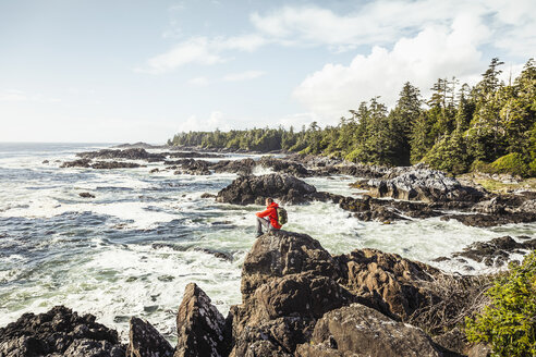 Male hiker looking out to sea from rocky coast, Wild Pacific Trail, Vancouver Island, British Columbia, Canada - CUF04093