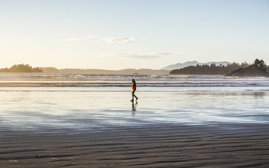 Man strolling on Long Beach at sunrise, Pacific Rim National Park, Vancouver Island, British Columbia, Canada - CUF04099