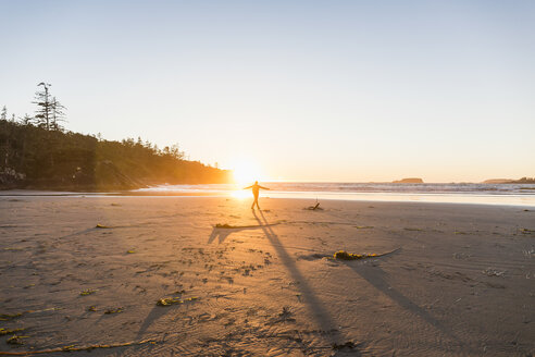 Man dancing on Long Beach at sunset, Pacific Rim National Park, Vancouver Island, British Columbia, Canada - CUF04105