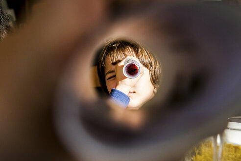 Portrait of boy looking at camera through rolled paper - CUF04144