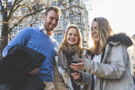 Young man and female friends looking at smartphone in city street - CUF04177