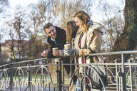 Young man and female friends standing chatting on park bridge - CUF04180