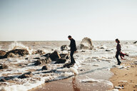 Mid adult couple standing on rocks at water's edge on beach, Odessa Oblast, Ukraine - ISF00930