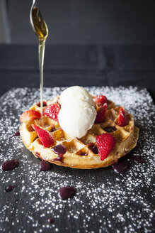 Spoon pouring maple syrup over strawberries and ice cream waffle on slate - CUF04275