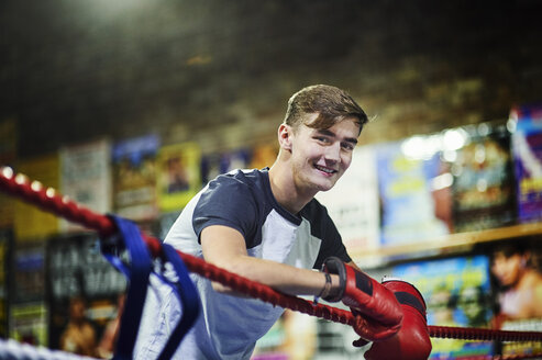 Portrait of young male boxer leaning against boxing ring ropes - CUF04317