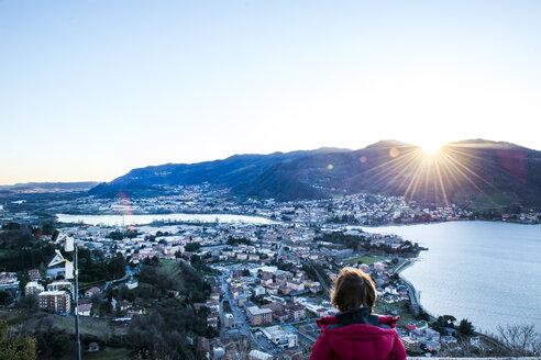 Rear view of boy watching sunset over mountains and town by lake, Italy - CUF04395