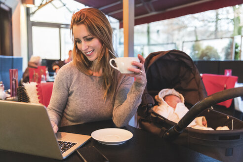 Mid adult woman in cafe looking at laptop by baby daughter in baby carriage - CUF04398
