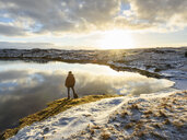 Man standing at water's edge, looking at view, rear view, Tjarnarholl, Iceland - CUF04413