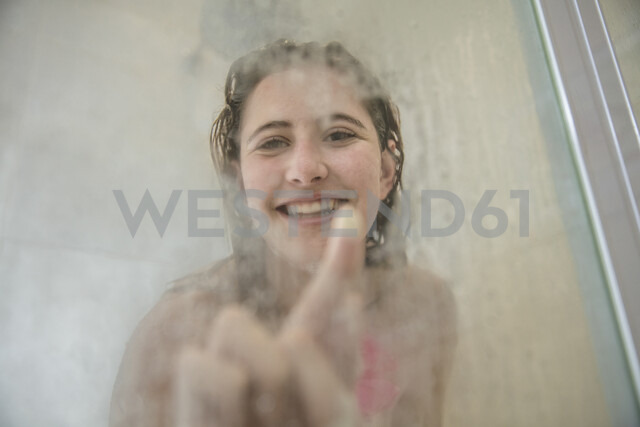 Portrait of young woman in shower drawing on steamed glass door - ISF00965