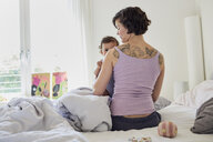Mother sitting on bed, holding baby girl, rear view - ISF01022