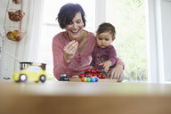 Mother holding baby girl at kitchen counter, pile of tomatoes in front of them - ISF01028