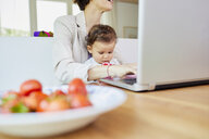 Mother using laptop with baby girl sitting on her lap - ISF01034