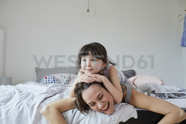 Mother and daughter lying on bed, daughter lying on mother's back - ISF01070 - Emely/Westend61