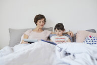 Mother and daughter relaxing in bed, daughter reading book, mother holding digital tablet - ISF01073