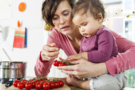 Mother and baby daughter in kitchen, sorting through tomatoes on kitchen counter - ISF01088
