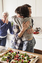 Mother and son hugging in kitchen, grandmother in background using smartphone - ISF01103