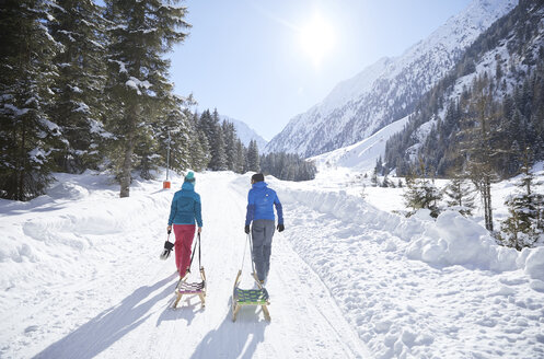 Couple with sledge walking in snow-covered landscape - CVF00472