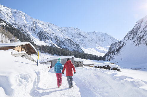 Couple walking in snow-covered landscape - CVF00481