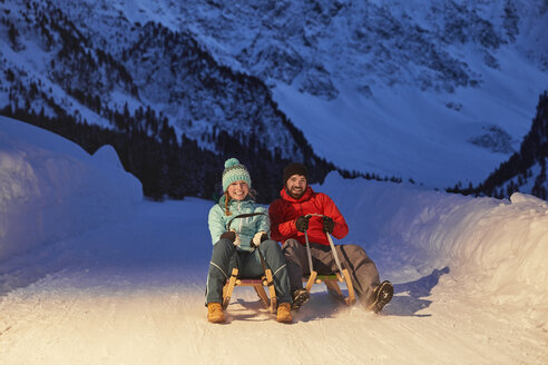 Happy couple sledding in snow-covered landscape at night - CVF00493