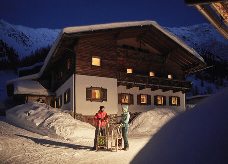 Couple with sledges in snow-covered landscape with rustic house at night - CVF00496