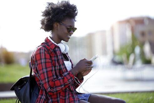 Smiling young woman with backpack and headphones using cell phone - JSRF00041