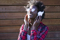 Portrait of smiling young woman listening music with headphones - JSRF00044