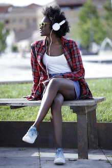 Portrait of young woman sitting on bench in city park listening music with headphones - JSRF00047