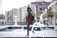 Young woman with backpack, smartphone and headphones walking in the city - JSRF00050