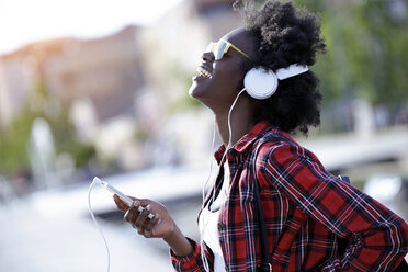 Portrait of laughing young woman using headphones and cell phone - JSRF00053