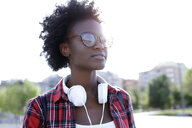 Portrait of young woman with headphones at backlight - JSRF00056
