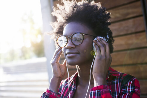 Portrait of smiling young woman listening music with headphones - JSRF00065
