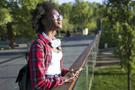 Young woman with headphones and cell phone standing on a bridge enjoying sunlight - JSRF00068
