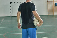 Rear view of indoor soccer player holding the ball - ZEDF01425