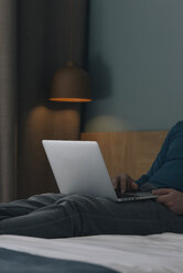Young man lying on bed using laptop, partial view - SKCF00451