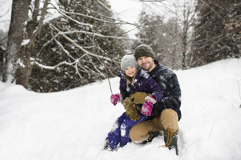 Portrait of mid adult man crouching in snow hugging daughter - CUF04534