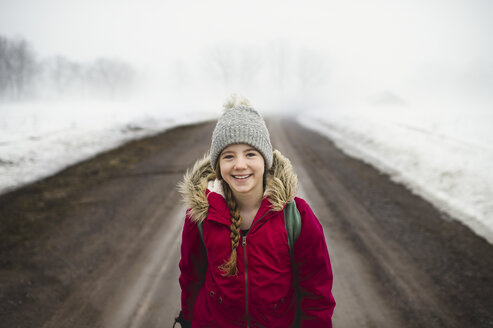 Portrait of girl in knit hat standing in middle of dirt road in fog - CUF04540