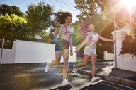 Teenage girls having fun in residential street, Cape Town, South Africa - CUF04681