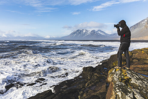 Man standing on rock, photographing view, Hvalnes. Iceland - CUF04723