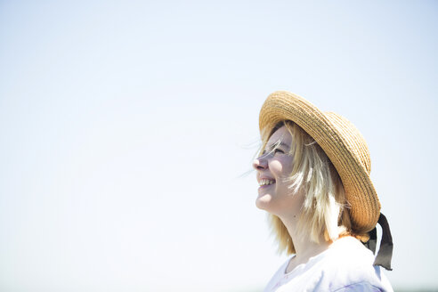 Young smiling woman with sun hat looking up, blue sky, copy space - FLLF00037