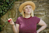 Portrait of young blonde woman with sun hat eating apple - FLLF00040