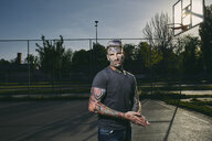 Portrait of tattooed young man on basketball court - ZEDF01428