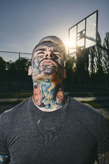 Portrait of tattooed young man on basketball court - ZEDF01437