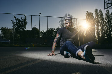 Portrait of tattooed young man sitting on basketball court at sunset - ZEDF01440