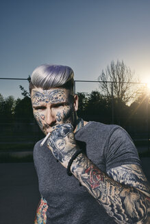 Portrait of tattooed young man smoking a cigarette - ZEDF01443