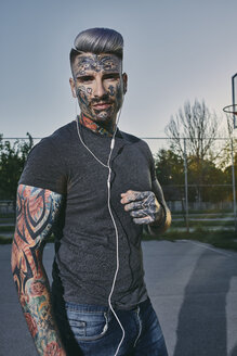Portrait of tattooed young man listening to music with earbuds - ZEDF01446