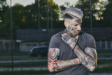 Portrait of tattooed young man outdoors - ZEDF01449