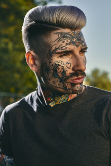 Portrait of tattooed young man outdoors - ZEDF01452