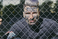 Portrait of tattooed young man behind fence - ZEDF01455