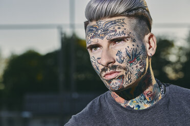 Portrait of tattooed young man outdoors - ZEDF01458